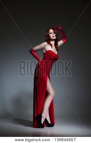 Beautiful young Woman with red hair dressed in red elegant dress