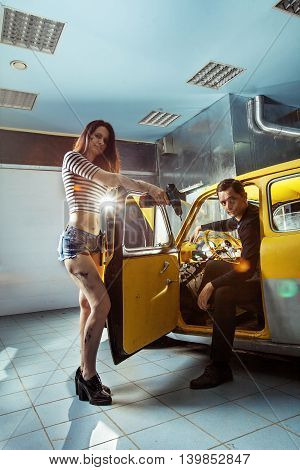 Woman Mechanic In Sexy Shirts With The Owner Of An An Old Car Are Looking At The Camera.