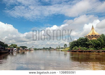 Landscape: River downstream through Town with green Banks and blue Sky with white Clouds