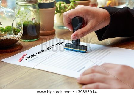 Hands holding rubber stamp with approved loan application on wooden desk.