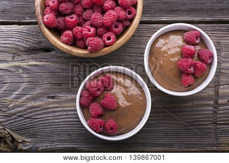 Chocolate Banana Smoothies served fresh juicy ripe raspberries with a sprig of mint in portioned bowls on a wooden background. The horizontal design