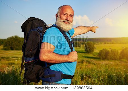 Physically fit handsome aged man with rucksack is pointing at beautiful sunset in the field and smiling