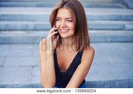Beautiful girl is sitting on street stairs and speaking on the mobile phone with a broad smile