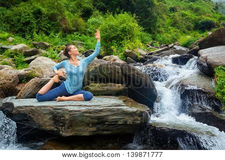 Young sporty fit woman doing yoga asana Eka pada rajakapotasana - one-legged king pigeon pose at tropical waterfall. Himachal Pradesh, India