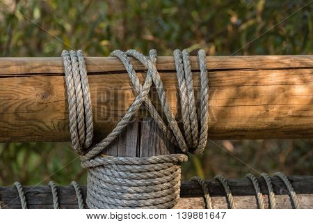 rail and post of wooden bridge tight together by rope knot