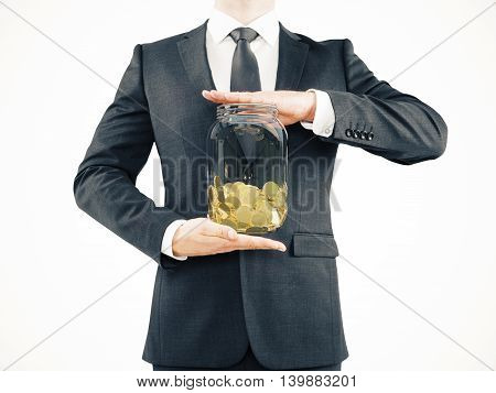Businessman in suit holding glass jar with golden coins on light background. Savings concept