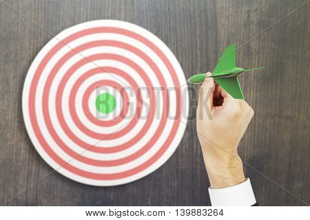Targeting concept with businessman hand playing darts on wooden background. 3D Rendering