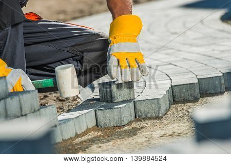 Brock Paving Closeup Photo. Construction Worker Paving Brick Pathway.