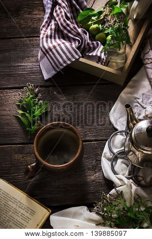 Cup Of Tea, Teapot And Book On Dark Wooden Background