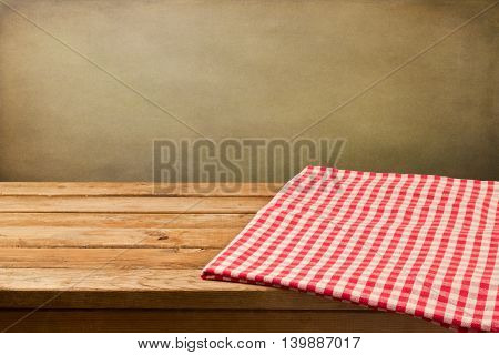 Background with empty wooden table covered with checked tablecloth