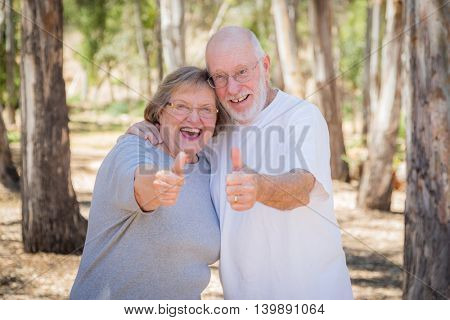 Happy Senior Couple With Thumbs Up Outdoors.