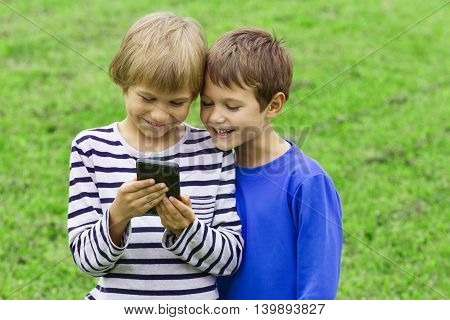 Children with mobile phone. Boys smiling, looking to phone, playing games or using application. Outdoor. Technology education leisure people concept