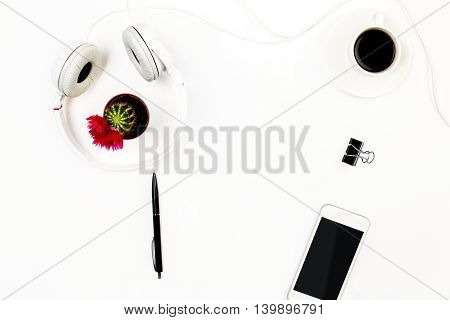 Top view of white desktop with blank mobile phone headphones small cactus pen peg and coffee cup. Mock up
