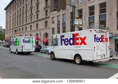 BOSTON,MASSACHUSETTS,USA - JULY 2,2016: FedEx Ground truck and FedEx Express truck on the same street in Boston. FedEx is one of the leading package delivery services.