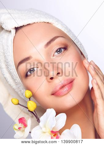 Portrait of beautiful girl touching her face with a towel on her head.