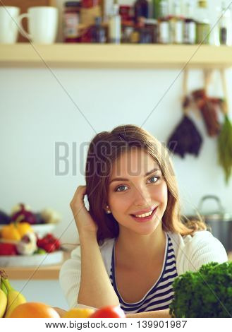 Young woman standing near desk in the kitchen.