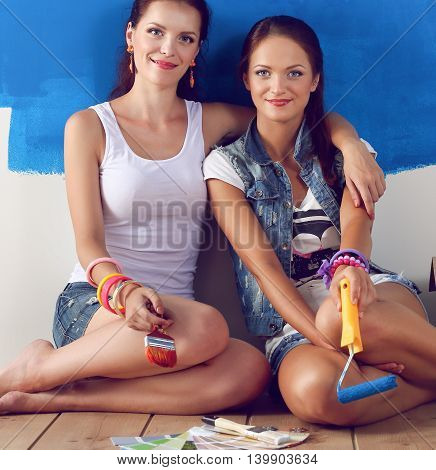 Two beautiful young woman doing wall painting, sitting on the floor.