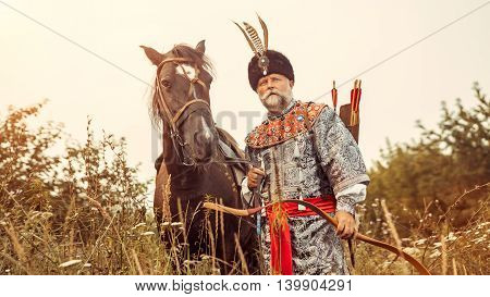Medieval nobleman with the bow in one hand and horse strap in other is hunting in the forest.