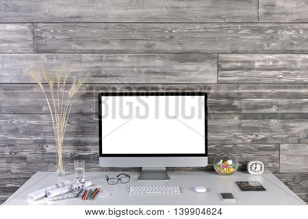 Creative hipster desktop with blank white computer monitor keyboard mouse tablet smartphone decorative stationery and other items on wooden plank wall background. Mock up