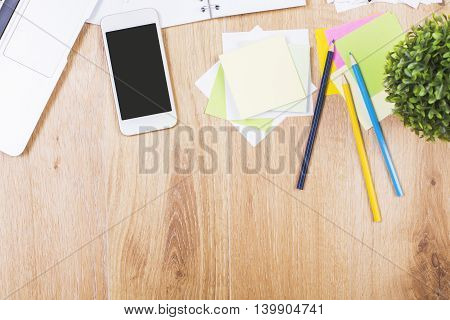 Top view of wooden office desktop with blank cellular phone plant and variety of colorful supplies. Mock up