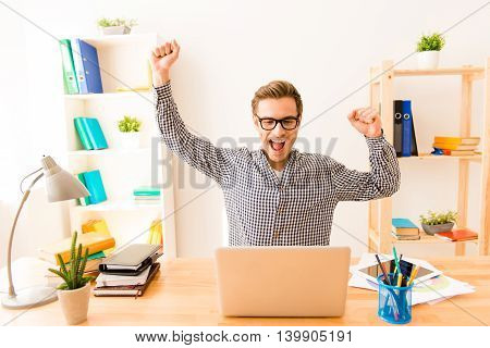 Happy Successful Young Businessman Triumphing With Raised Hands