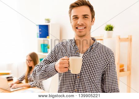 Smiling Man Drinking Coffee While His Secretary Typing On Laptop