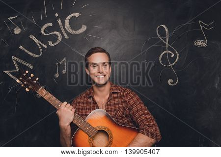 Portrait of happy smiling man holding the guitar