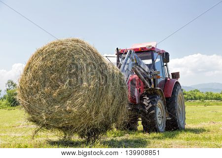 Tractor collecting hay bales in the fields
