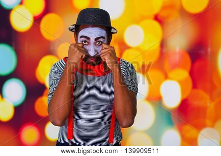 Headshot pantomime man with facial paint posing for camera using hands interacting rubbing eyes, blurry lights background.