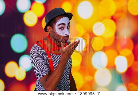 Headshot pantomime man with facial paint posing for camera using hands interacting, blurry lights background.