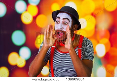 Headshot pantomime man with facial paint posing for camera using hands around mouth yelling, blurry lights background.