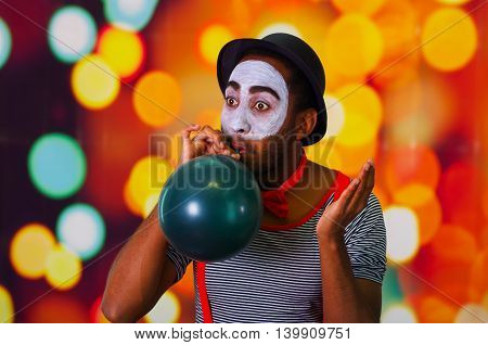 Pantomime man with facial paint posing for camera blowing up balloon, blurry lights background.