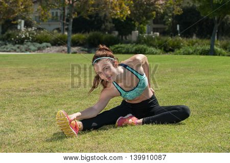 Attractive female athlete maintaining her flexibility in the grass.