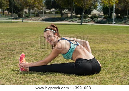 Attractive teen athlete stretching her leg on the grass.