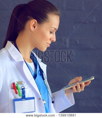 Young woman doctor standing with your phone