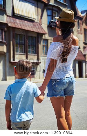 Back view of young mother with small son holding hands and taking a picture of old building during their walk in the city