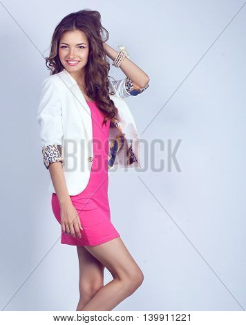 Young woman wearing a pink dress standing
