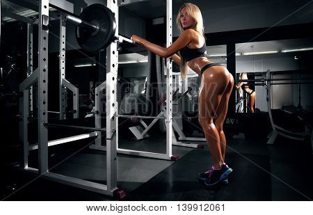 Back view of blondi sexy fitness girl in sport wear with perfect body in the gym posing.