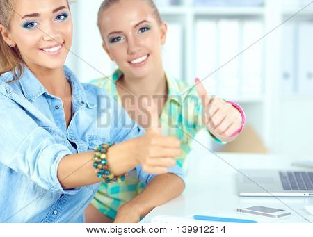Two women working together at office, sitting on the desk and showing ok