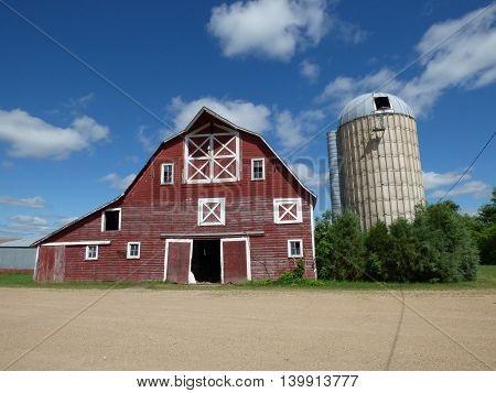An abandoned old barn and a leaning silo.