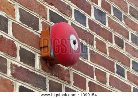 Red fire alarm on a brick wall.