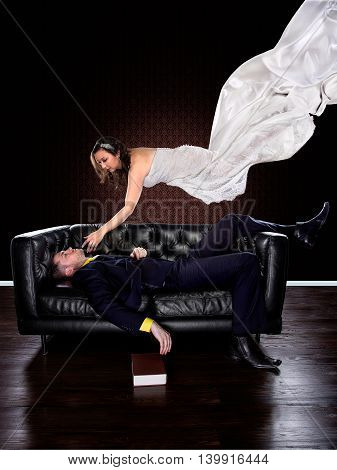 Man dreaming on a couch of a girl in a wedding dress floating and descending to him