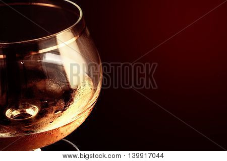 Close up of alcohol in a glass glass against a dark background. Liquid alcohol of caramel color close up. A glass transparent with patches of light. Indoors. Horizontal format. Color. Photo.