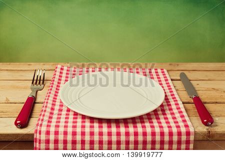 Empty plate with knife and fork on checked tablecloth over green background