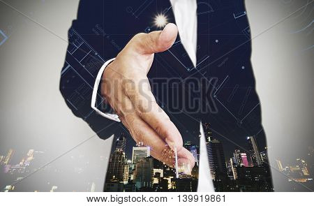 Businessman extending hand with city at night and architectural drawing background