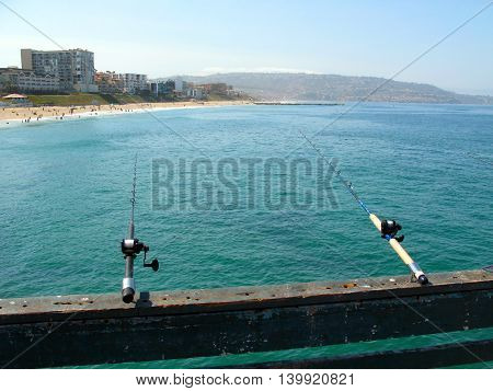 Fishing off Redondo Beach pier in California with beach and blue ocean in background.