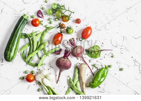 Assortment of fresh vegetables on a light background - zucchini peppers beets tomatoes green beans onion. Food background. Free space for text top view