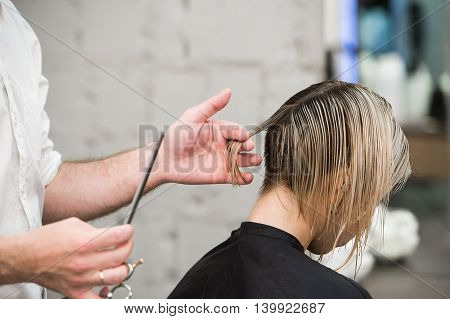 hairdresser cuts hair with scissors on crown of handsome satisfied client in professional hairdressing salon.