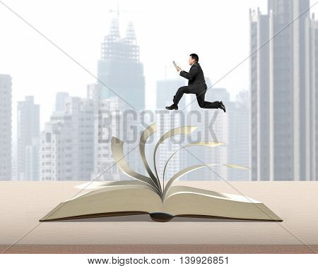 Man Holding Tablet Running On Top Of Flipping Pages Of Open Book