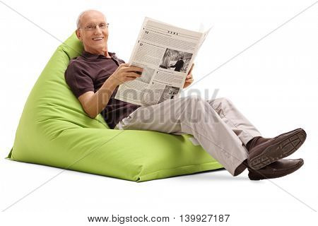 Joyful senior holding a newspaper and sitting on a green beanbag isolated on white background